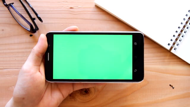 hand using mobile phone with green screen on wooden office table - top view - projection screen stock videos and b-roll footage