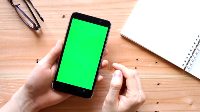 hand using mobile phone with green screen on wooden office table - top view