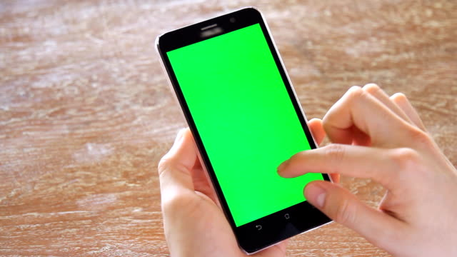 hand using mobile phone with green screen on wooden office table