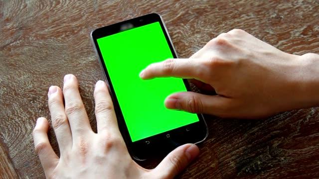Hand mit Mobiltelefon mit Greenscreen auf Holztisch