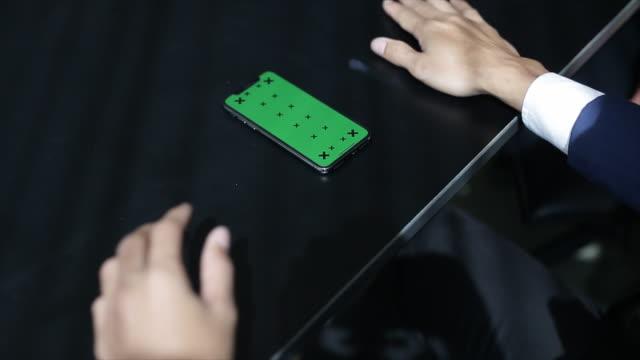 vídeos y material grabado en eventos de stock de mano con teléfono móvil con pantalla verde en la mesa de madera - vista por la espalda
