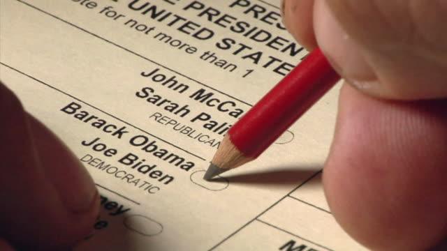 vídeos de stock e filmes b-roll de cu hand using pencil to vote for john mccain and sarah palin on us presidential ballot / pencil moves between choices before deciding - escrita ocidental