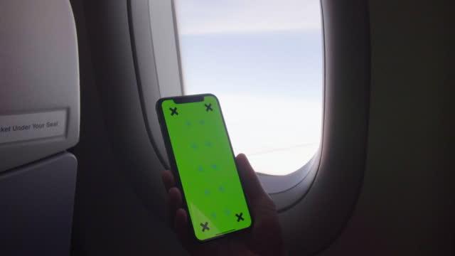 vidéos et rushes de main utilisant le smartphone sur l'écran vert d'avion - passager
