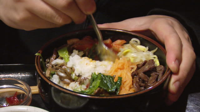 CU Hand using spoon to mix bowl of food containing rice, bean sprouts, vegetables, egg, and meat/ Tokyo, Japan