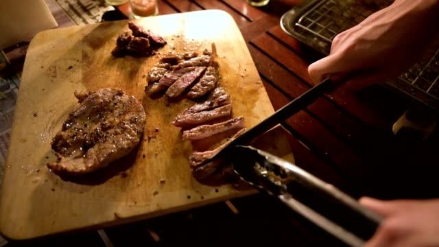 vídeos y material grabado en eventos de stock de uso manual con cuchilla cortando filete de ternera a la parrilla en tabla de cortar - jugoso