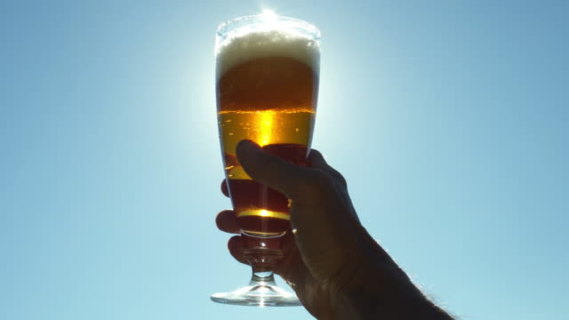 hand with a glass of beer in the sun - beer glass stock videos & royalty-free footage