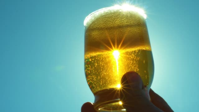 stockvideo's en b-roll-footage met hand met een glas bier in de zon - alcohol