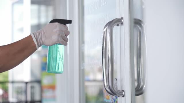 vídeos de stock, filmes e b-roll de slo mo mão com luva pulverizando álcool para armazenar porta para desinfetar o vírus covid-19. - limpo