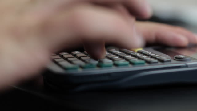 Hand with light complexion pushing buttons on a TI scientific calculator side profile