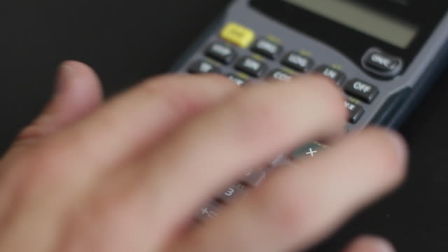 Hand with light complexion pushing buttons on a TI scientific calculator