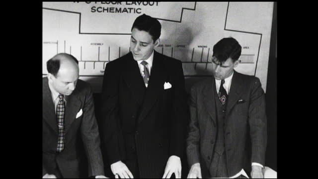 "hand with pointer indicate details on diagram labeled ""w-6 floor layout schematic""; three men in suit discussing plans in front of diagram - 1940 1949 video stock e b–roll"