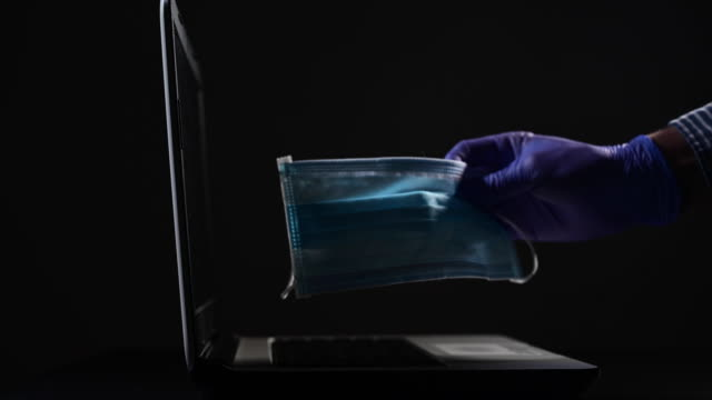 hand with protective gloves holding a protective mask close to a laptop. virus concept. - schutzhandschuh stock-videos und b-roll-filmmaterial