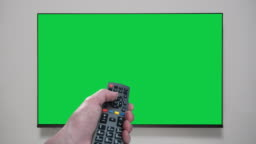 4K - Hand with remote control changes channels tv. Green screen. Chroma key