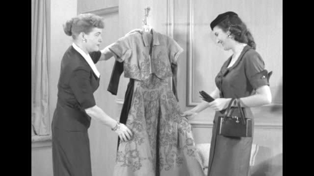 Hand with scene indicator Vail / Women in sitting room with potted plants look at dresses hanging on stand at the Shamrock Hotel they select one...