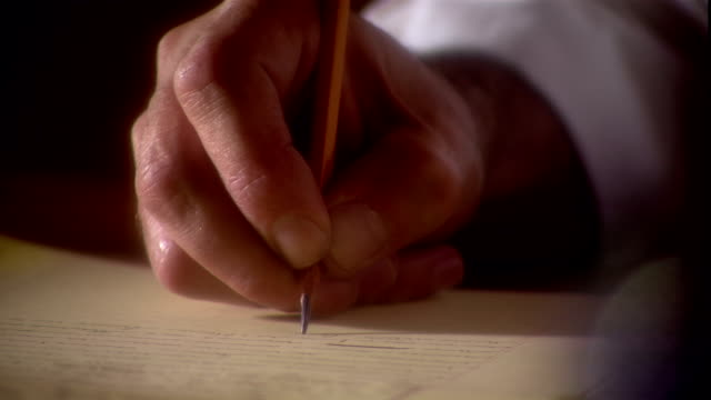 a hand writes with a pencil on a yellow pad of paper. - author stock videos & royalty-free footage