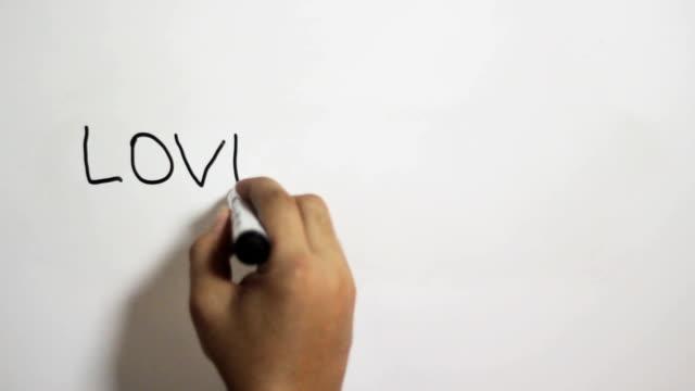 vidéos et rushes de main qui écrit un message de «l'amour est rare» sur un tableau blanc à l'aide d'un marqueur noir - stylo