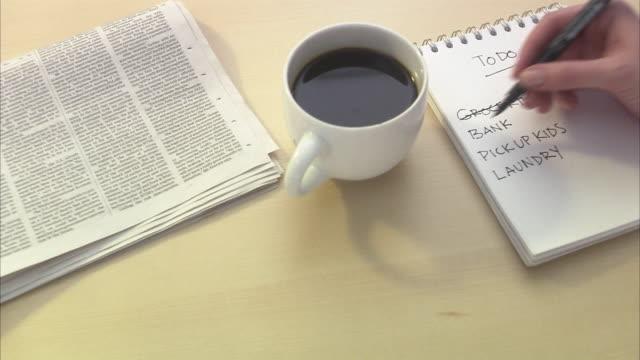 vídeos de stock, filmes e b-roll de a hand writing a note. - manhã