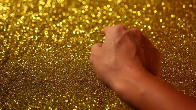 vídeos y material grabado en eventos de stock de mano escribiendo en la señal de pare, sobre fondo de arena dorada - símbolo de arroba