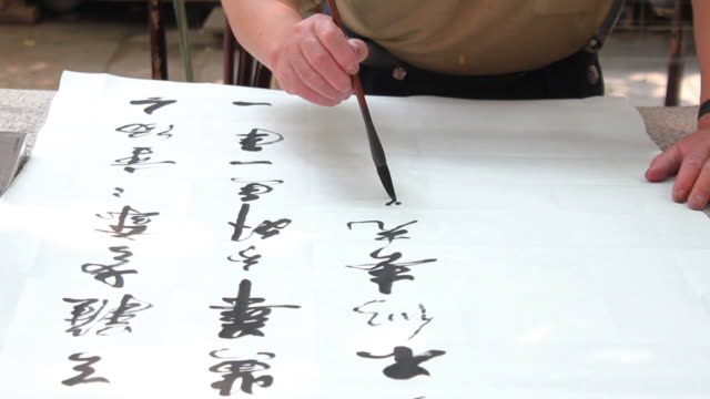 ms hand writing chinese calligraphy in black ink on rice paper/xian,shaanxi,china - washi paper stock videos & royalty-free footage
