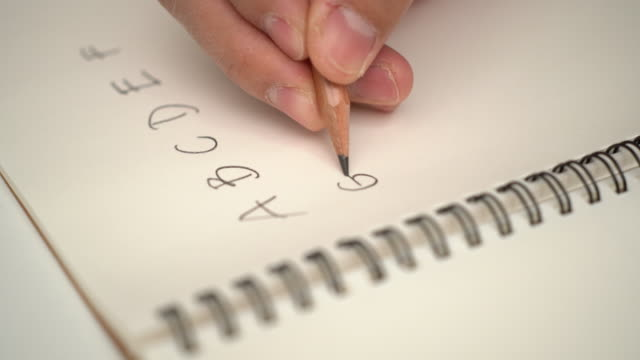 hand skriva engelska alfabetet på anteckningsboken med en penna - stor bokstav bildbanksvideor och videomaterial från bakom kulisserna