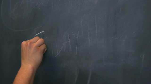 """CU Hand writing """"Friday"""" on black chalkboard"""