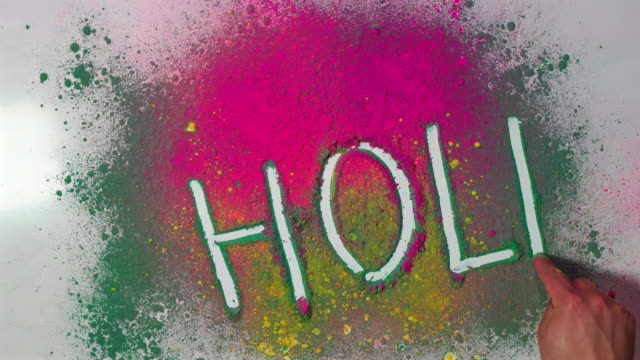 a hand writing 'holi' on a table with different coloured dry powder, during the holi festival - water fight stock videos & royalty-free footage