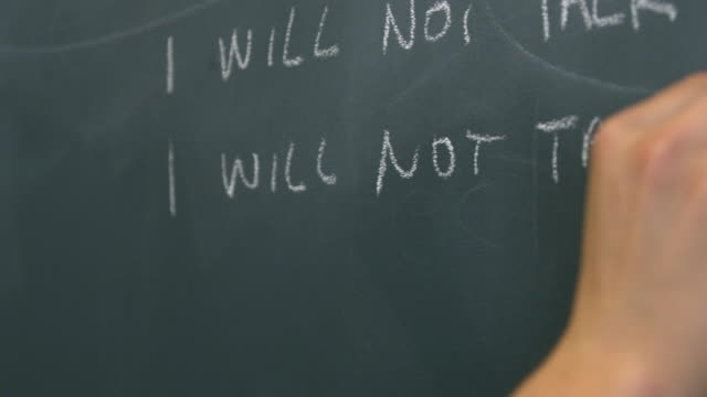 "cu hand writing ""i will not talk in class"" on black chalkboard - english language stock videos and b-roll footage"