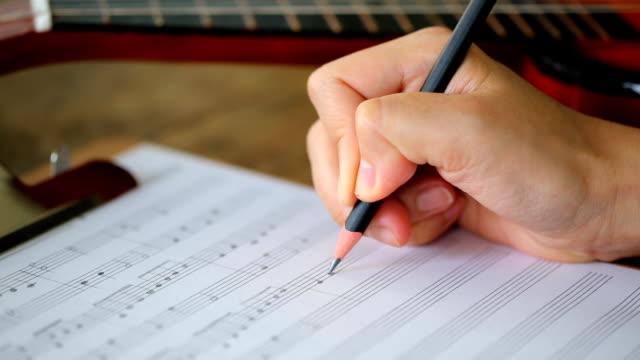 vidéos et rushes de main écrire notes de musique (travelling sur chariot) - partition musicale