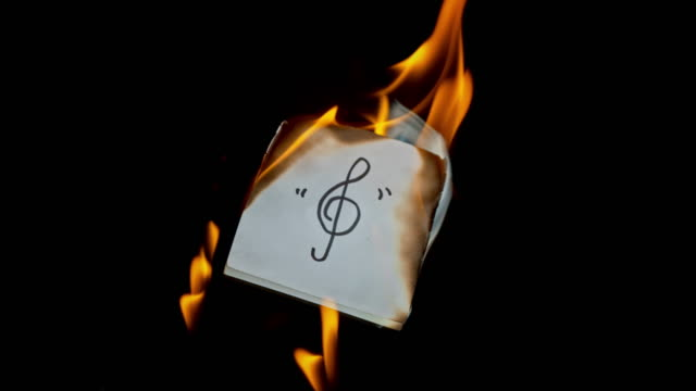slo mo ld hand written treble clef symbol burning on a piece of paper - treble clef stock videos & royalty-free footage