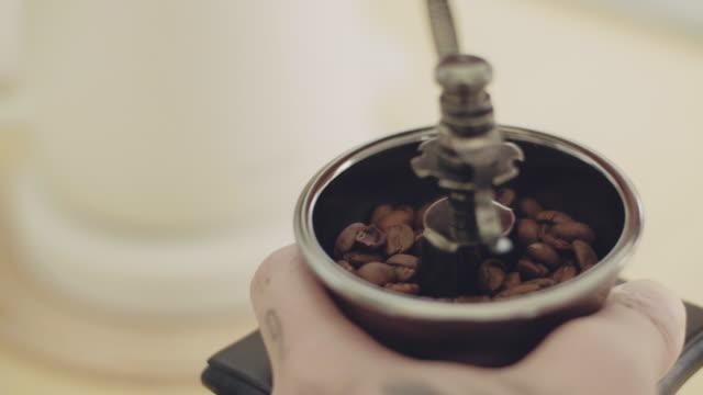 手の若いアジアの男はコーヒーグラインダーを使用します - 挽く点の映像素材/bロール