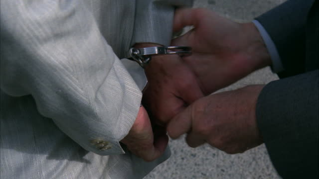 vidéos et rushes de ms handcuff being inserted in hand - arrestation