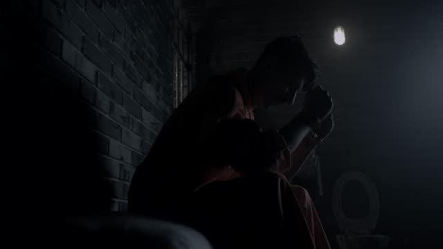 手錠をかけられ男性刑務所でベッドの上に座って - 刑務所点の映像素材/bロール