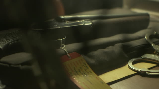 Handcuffs and sawed-off shotgun with evidence tag