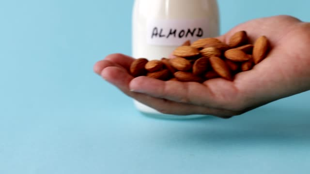 handful of almonds and almond milk on blue background - milk jug stock videos & royalty-free footage