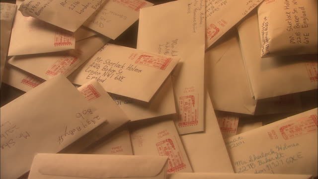 a handful of envelopes fall onto a pile of other letters, all addressed to sherlock holmes on baker street. - sherlock holmes stock videos & royalty-free footage