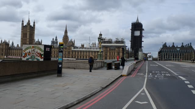a handful of people walk over a quiet westminster bridge during the coronavirus pandemic on march 20 2020 in london england - brian dayle coronavirus stock videos & royalty-free footage