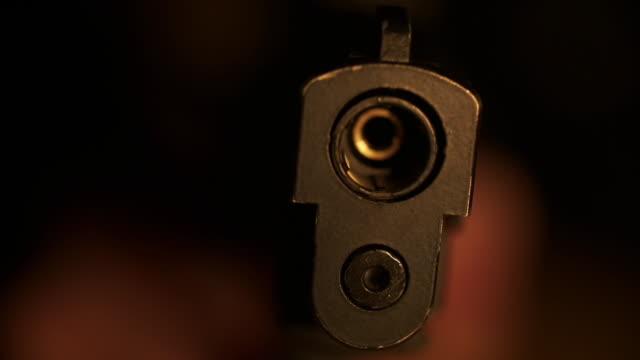 CU of handgun muzzle pointed at camera
