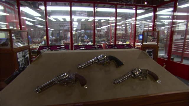 vídeos de stock e filmes b-roll de handguns hang on display near factory workers. - cristaleira