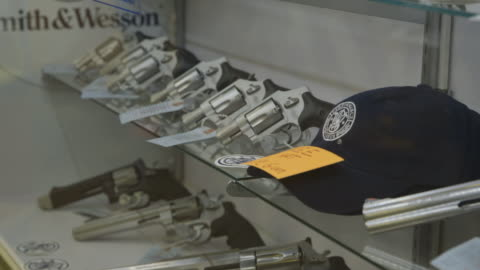 handguns in glass case of gun shop, medium shot - 銃器店点の映像素材/bロール