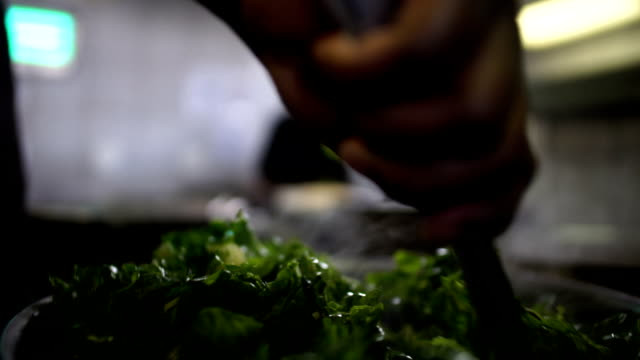 vídeos de stock e filmes b-roll de handheld slo mo african ethnicity chef cooking spinach leaves in bulk/ johannesburg/ south africa - panela utensílio