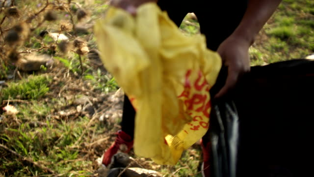 handheld slo mo african ethnicity hand throwing waste into black garbage bag/ johannesburg/ south africa - unknown gender stock videos & royalty-free footage