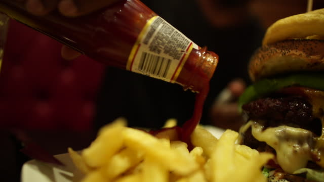 handheld cu slo mo african ethnicity male hand pouring ketchup onto chips/ johannesburg/ south africa - ketchup stock videos and b-roll footage