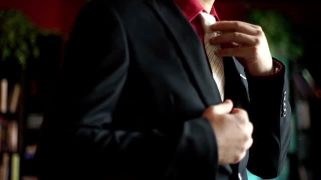 MS Hand-held : Businessman in black suit is adjusting his necktie.