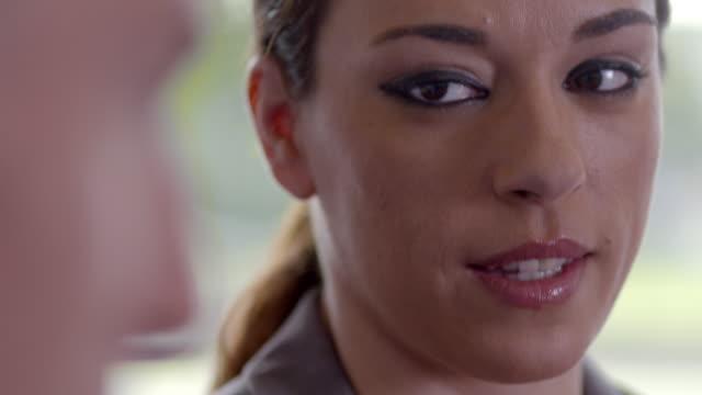 CU handheld businesswoman talking, dirty frame shallow depth of field