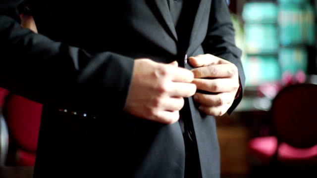 MS Hand-held Camera : A man in black suit buttoning his jacket with blurred background.