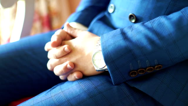 CU Hand-held Camera : Elegant groom in a navy blue suit sitting with his hands clasping while waiting for a bride.