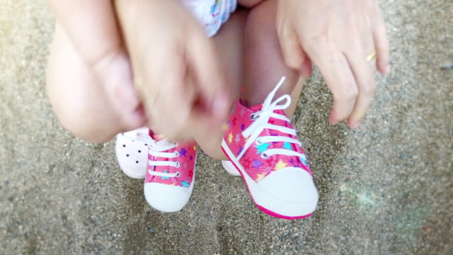 cu hand-held camera of hand's mother helping her baby to put shoes outdoors. - footwear stock videos & royalty-free footage