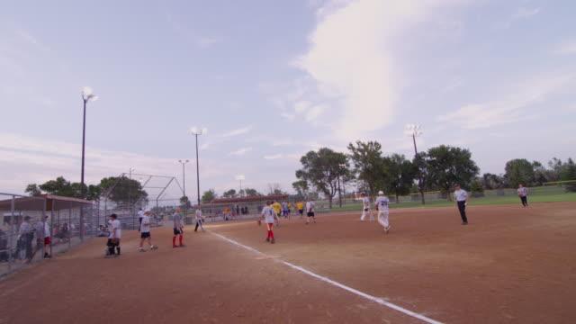 vídeos y material grabado en eventos de stock de handheld camera players congratulate each other at the end of a men's league softball game. - sófbol