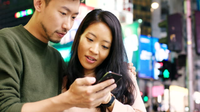 vídeos y material grabado en eventos de stock de slo mo handheld close up de una pareja joven revisando un teléfono inteligente afuera por la noche - 25 29 años