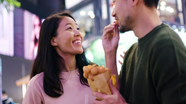 slo mo handheld close up of a young couple eating traditional street food in hong kong - young couple stock videos & royalty-free footage